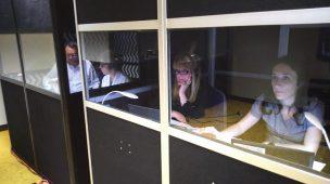 Tradutores em cabine de interpretação simultânea.